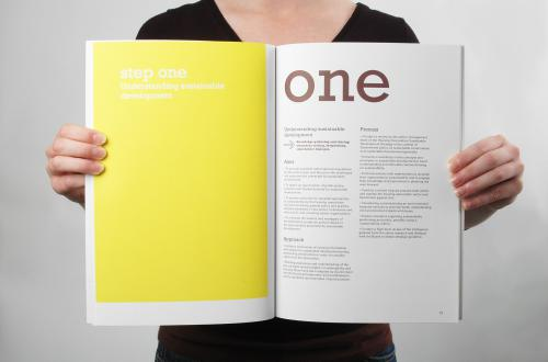 "a person in a black shirt holding up a book. On the left-hand side of the book is a yellow page that read ""step one"" in white font. On the right-hand site is a white page with the word ""one"" written in large brown font."