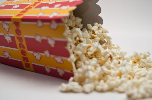 Popcorn spilling from red and yellow movie-theatre-style box, on a white background