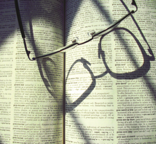A picture of an open dictionary page with eyeglasses on top.